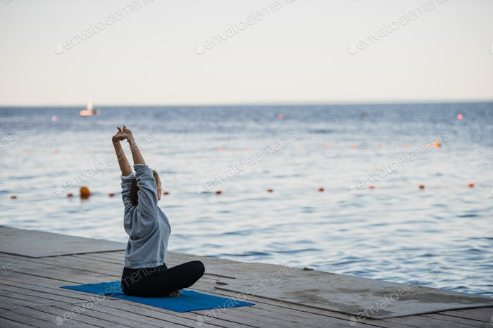 Thumbnail for Morning shot of a girl in lotus position doing stretching yoga exercises on the pier
