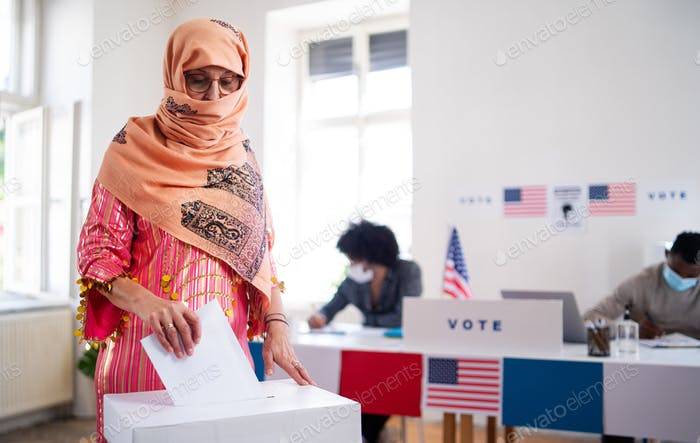 Islamic woman voter putting her vote in the ballot box, usa elections and coronavirus