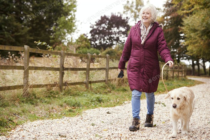 Active Senior Woman On Autumn Walk With Dog On Path Through Countryside