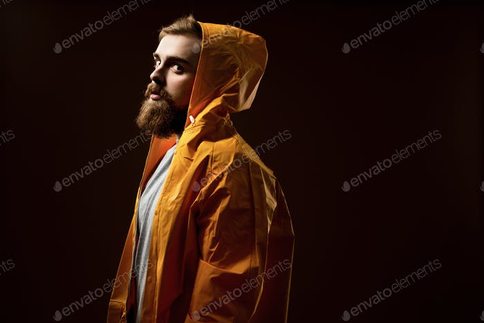Guy with a beard and mustache dressed in a gray t-shirt and yellow jacket with a hood is standing on