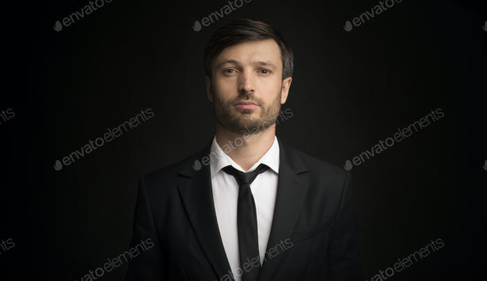 Portrait Of Serious Businessman Looking At Camera, Black Background