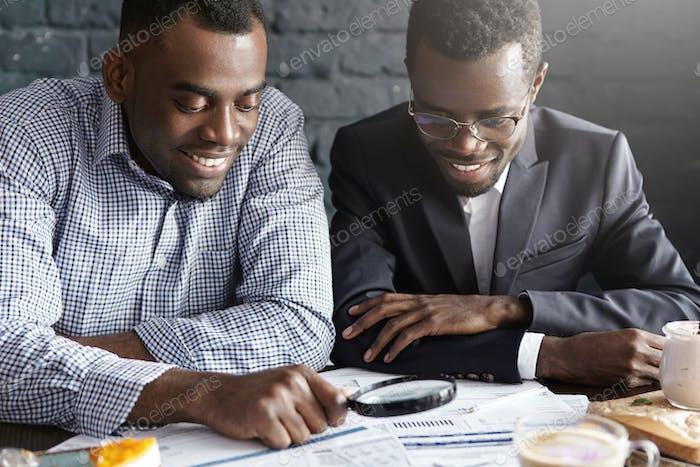 Dos felices hombres de negocios de piel oscura leyendo documentos con lupa, analizando el agre financiero