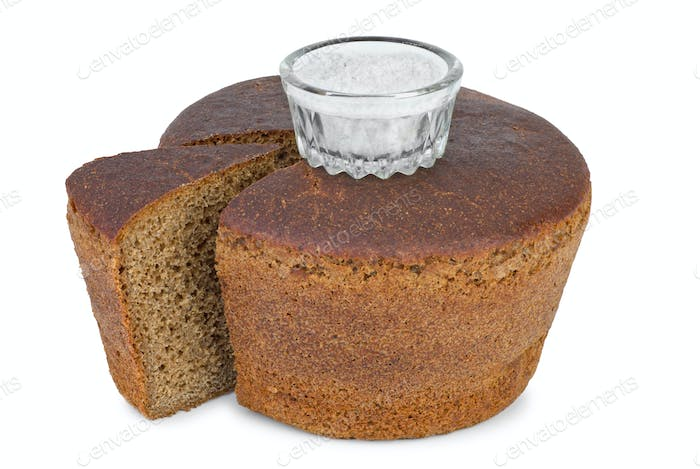 Cut loaf of round rye bread and salt jar