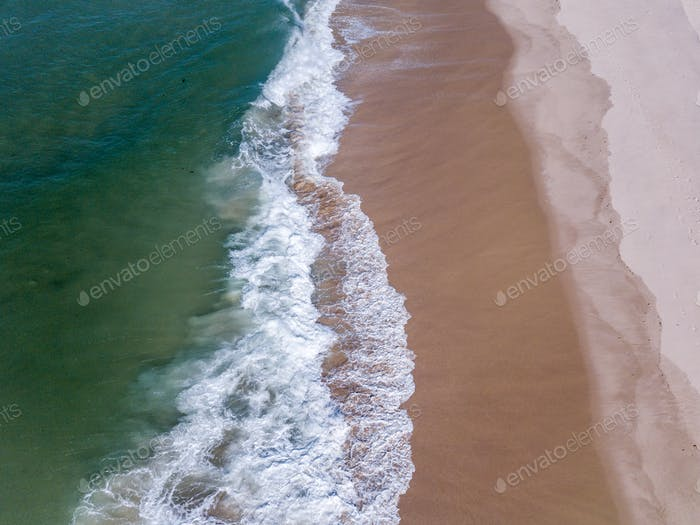 Drone picture of waves hitting the beach.