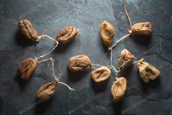 Dried figs with a string on a gray stone
