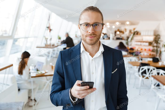 Businessman indoors in office using mobile phone.