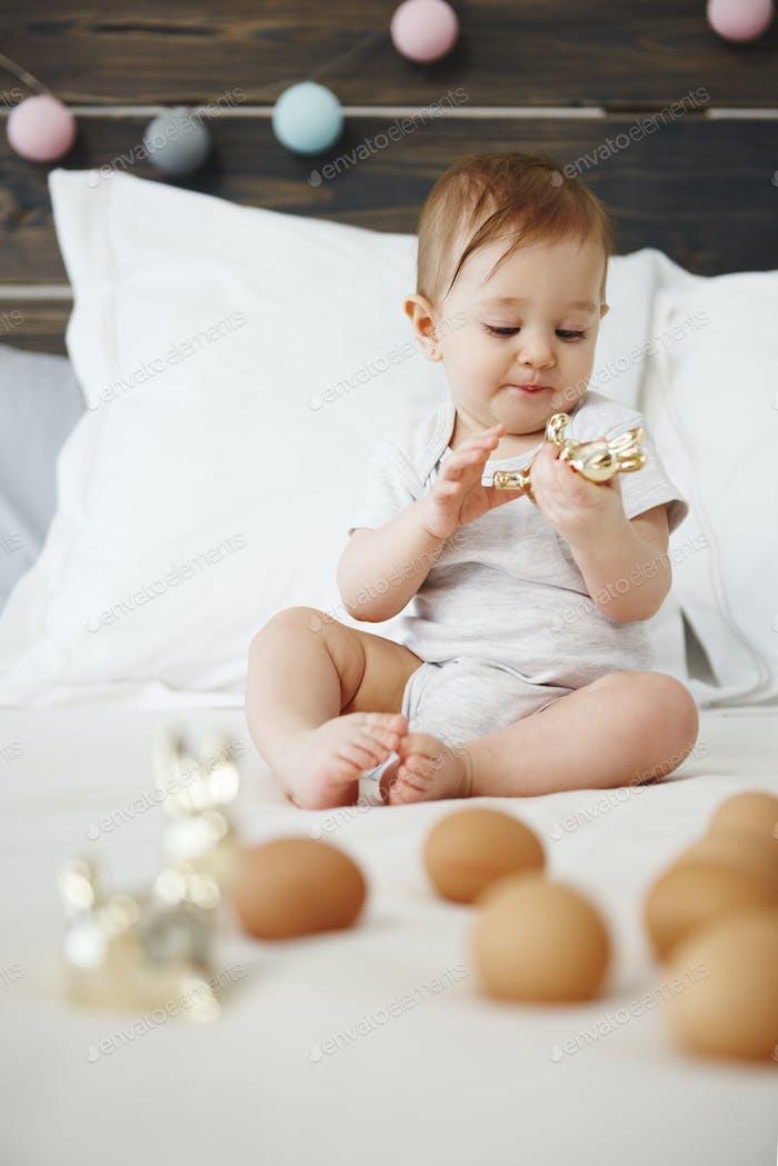 Baby spielt mit Spielzeug auf dem Bett