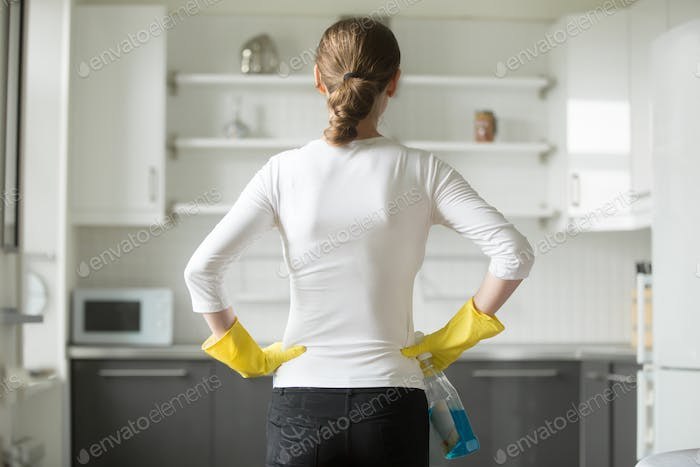 Rear view of woman hands at her hips, observing kitchen