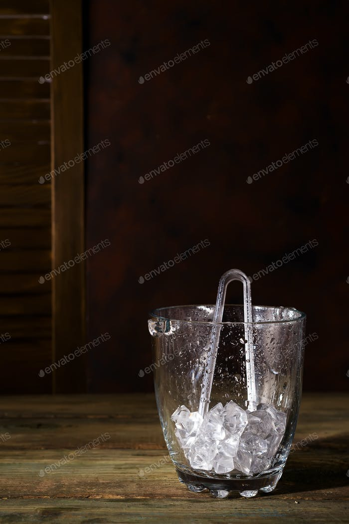 Champagne bucket full with ice on dark wooden background, shadows and copy space