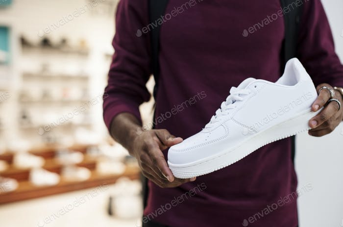 African man holding a white sneaker