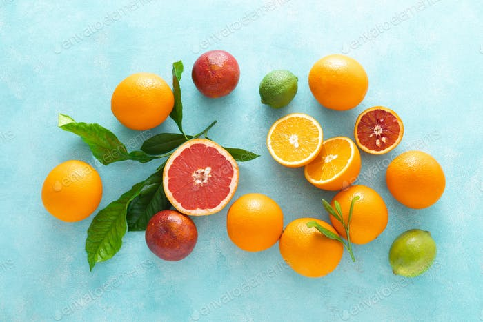 Various tropical fruits composition with leaves, flat lay blue summer background, top view