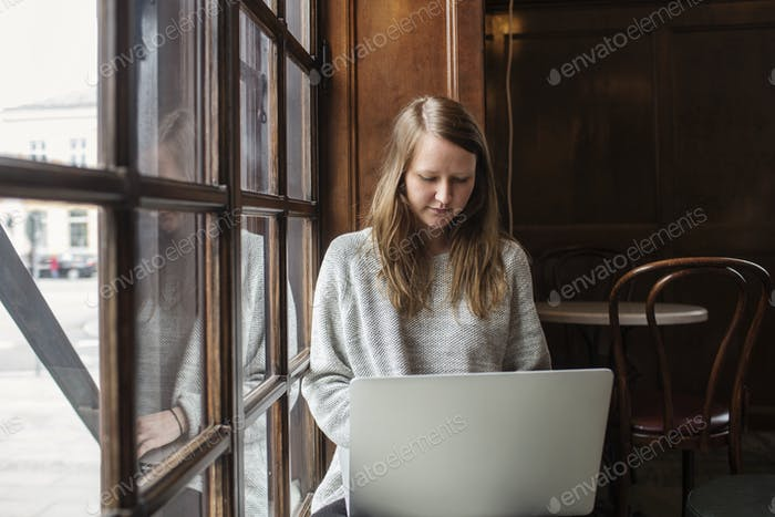 Thoughtful woman using laptop while sitting at cafe