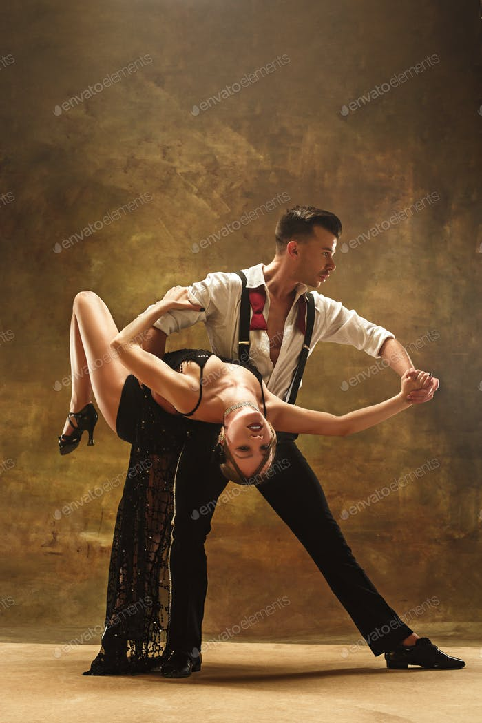 Flexible young modern dance couple posing in studio.