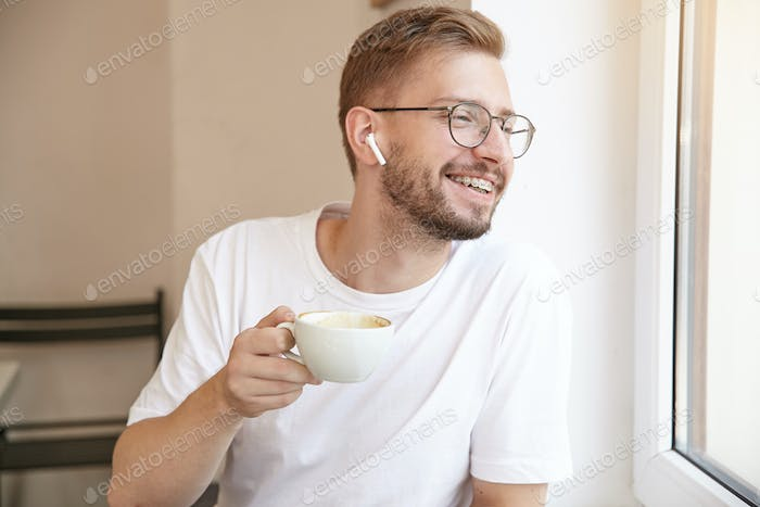 Good looking bearded guy looking to the window and drinking coffee while listening