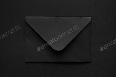 Black envelope on a black background.