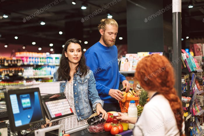 Young beautiful couple standing near cashier desk while buying p