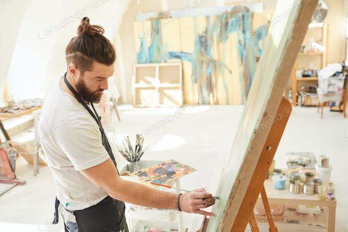 Bearded Artist Painting on Easel in Studio
