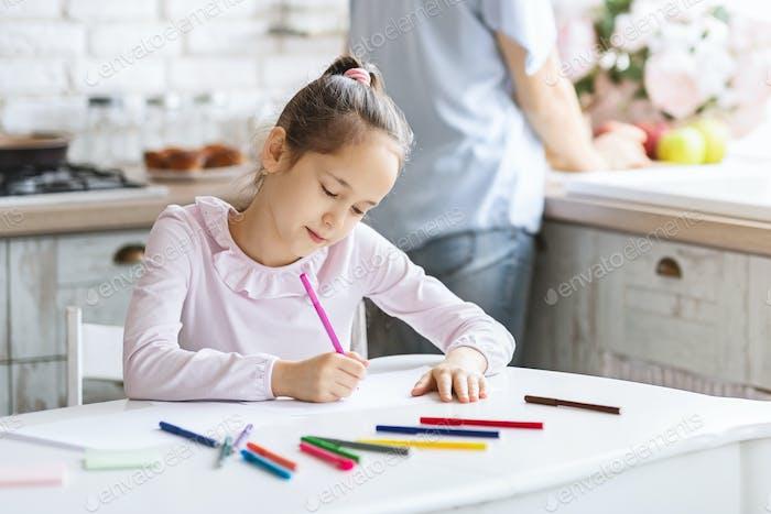 bastante pequeña chica ocupado con dibujo en cocina mesa