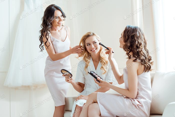 bridesmaids preparing bride for ceremony and doing makeup