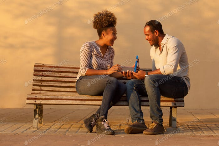 portrait of happy couple sitting on bench with man giving annive