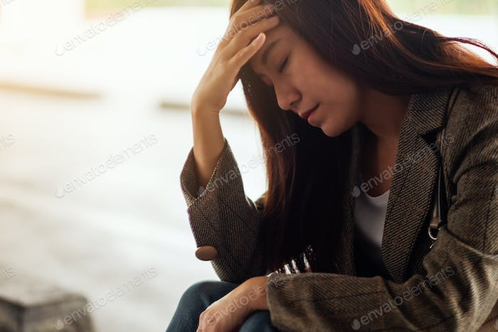 A stressed young asian woman sitting alone