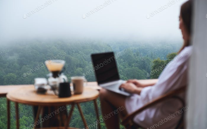 A woman using and working on laptop computer while sitting on balcony with a nature view