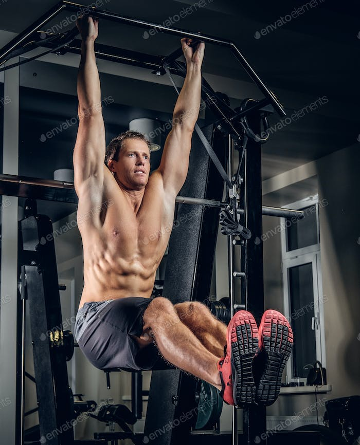 A man doing ABS workouts on pull up bar.
