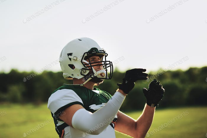 American football receiver about to catch a ball during practice