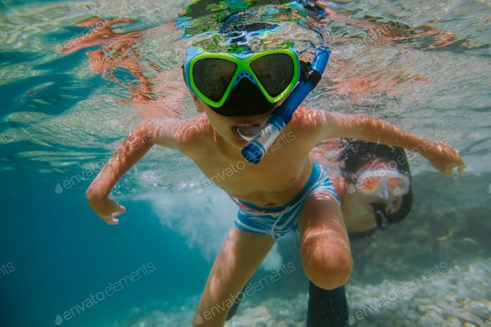 Child learning to snorkel with his mother in sea.