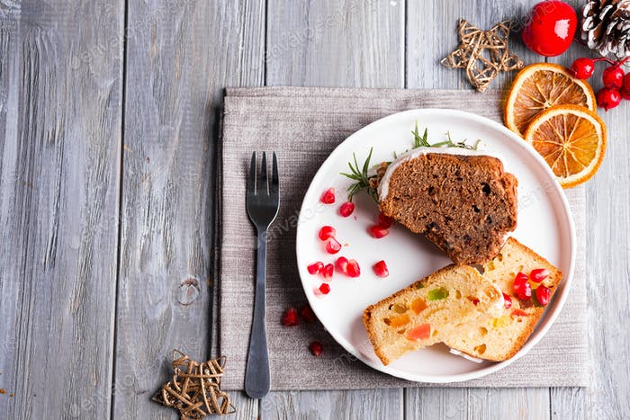 Christmas sliced chocolate cake and fruit cake with white icing and pomegranate kernels on plate