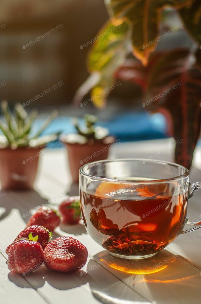 Bild von Glas Tasse Tee, rote Erdbeeren, Blumen in Töpfen auf einem hellen Holztisch.