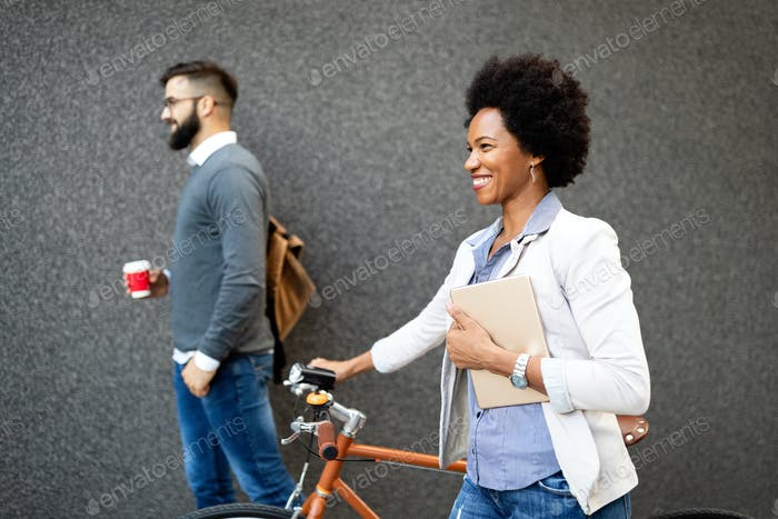 Happy cheerful businesswoman going to work by bicycle