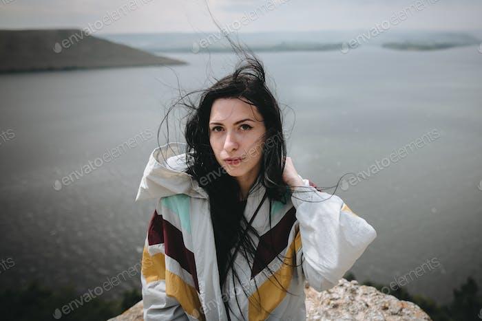 Молодая туристка отдыхает на скале