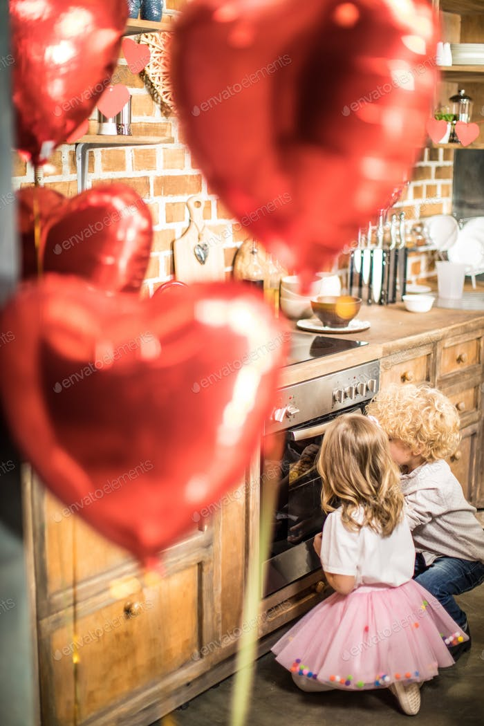 View through air ballons of little boy and girl looking in oven in kitchen