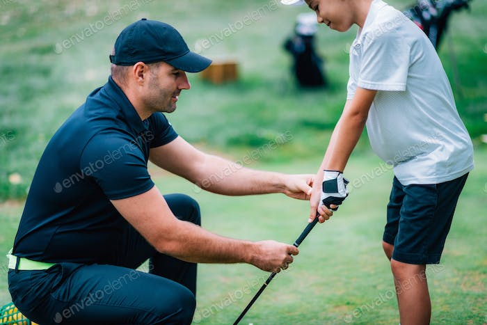 Golf Instructor adjusting young boy's grip