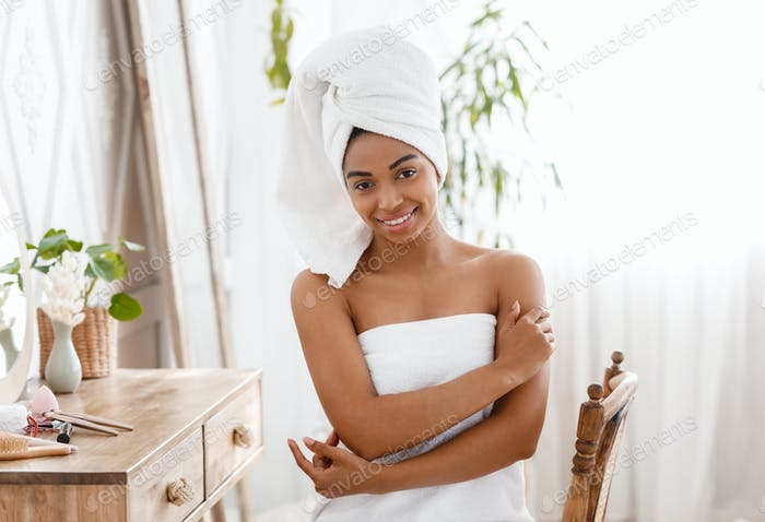 Self Care Day. Beautiful african girl wrapped in towel posing in bedroom