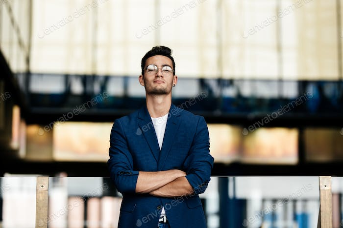 Architect in stylish clothes stands on the background of a modern glass building