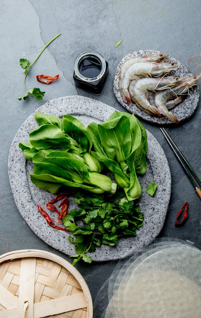 Asian cooking ingredients: rice noodles, pok choy, sauces, raw shrimps.