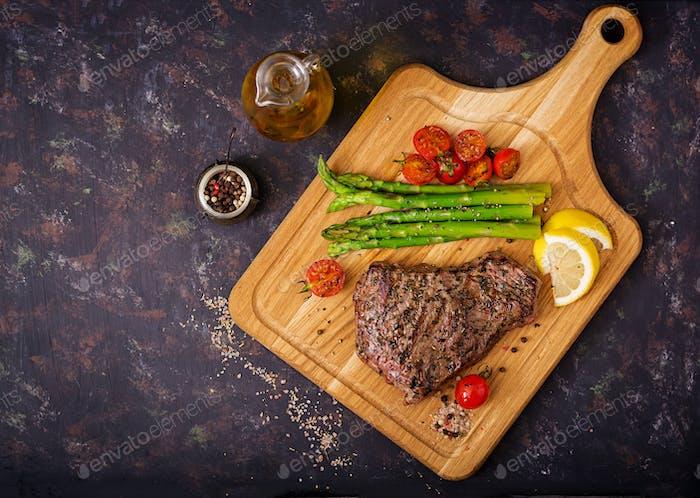 Saftiges Steak seltenes Rindfleisch mit Gewürzen auf einem Holzbrett und Garnierung von Spargel. Flache Lag. Ansicht von oben