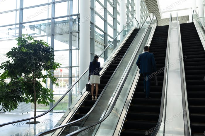 Rear view of  mixed-race businessman and businesswoman moving upwards on escalator in office