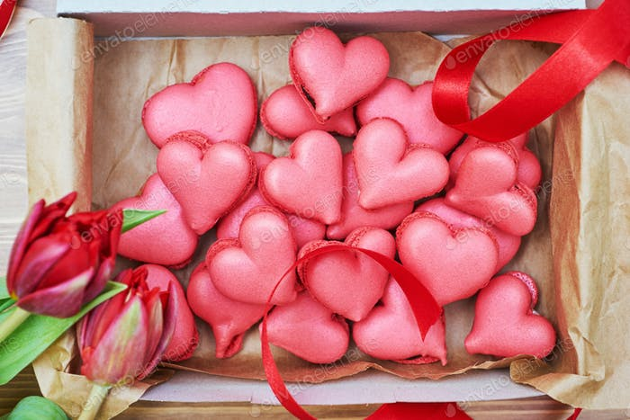 The box of heart-shaped macarons with flowers and ribbon on a wooden table.