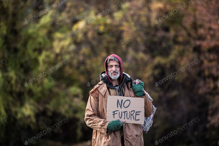 Homeless beggar man standing outdoors in park, holding bag and cardboard sign.