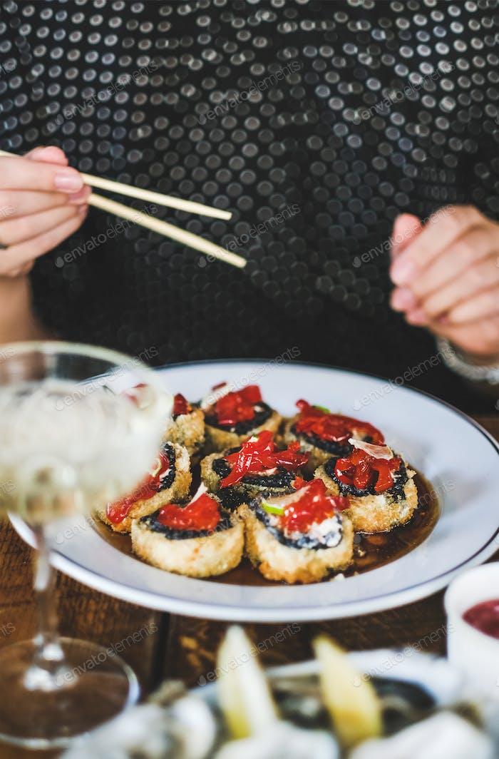 Girl eating baked susi maki with chopsticks at Japanese restaurant