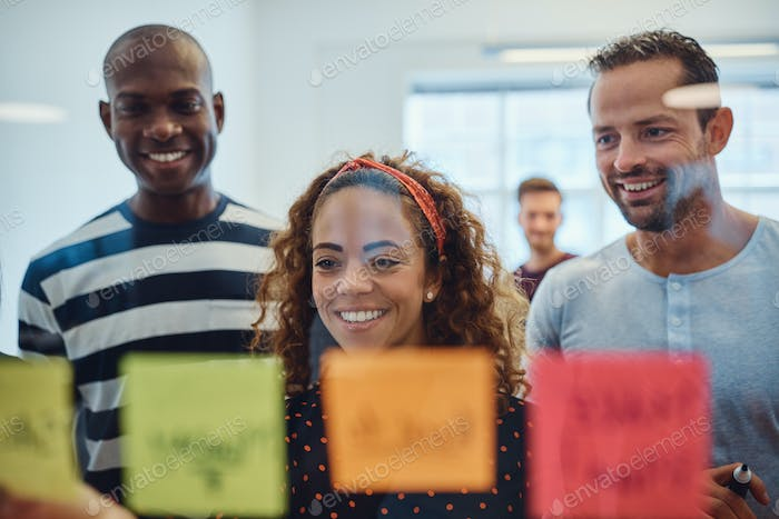 Smiling work colleagues brainstorming with sticky notes in an office