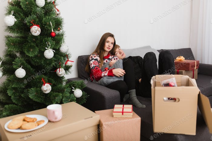 Beautiful young couple sitting on sofa at home while spending time together with Christmas tree near