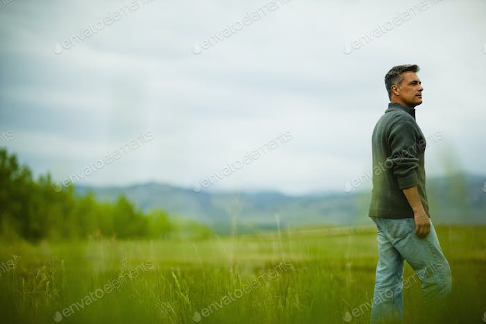 A man standing alone looking into the distance, deep in thought.