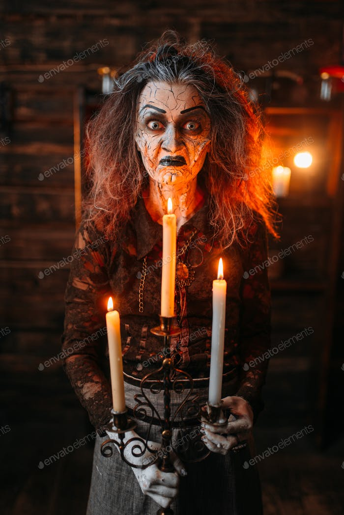 Scary witch with candlestick and cane reads spell