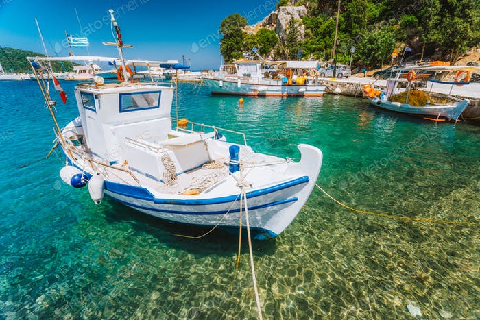 Traditional fishing boat in crystal clear Mediterranean sea cove of Ithaka island, Greece