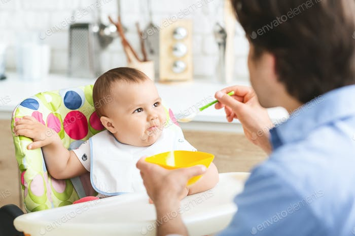 Hungry baby eating healthy kid food in kitchen