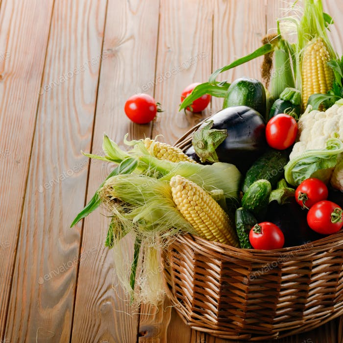 Organic vegetable food ingredients in the basket on wood backgro